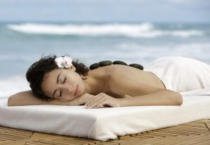 attractive woman enjoying a heat stone massage on the beach